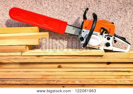 Near the wall of the house on the sawn boards is a modern and powerful chainsaw.