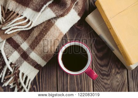 Vinous mug of black coffee in a winter day soft plaid yellow and beige books. Selective focus and top view