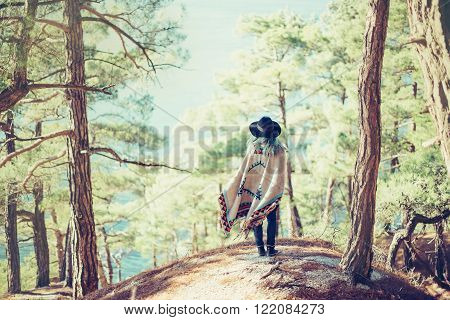 Fashionable young woman wearing in hat and poncho standing on coast in the forest among pine trees and looking at sea rear view