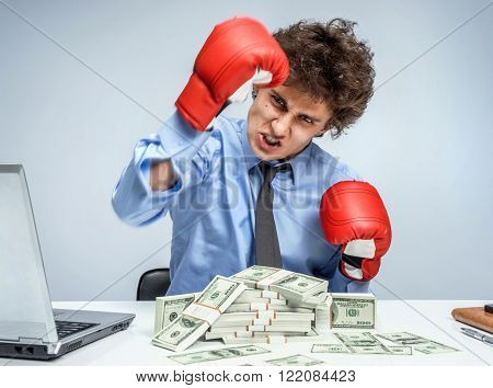 Victory in business - business concept showing aggressive male businessperson flexing muscles wearing boxing gloves isolated on grey background. Mad businessman.