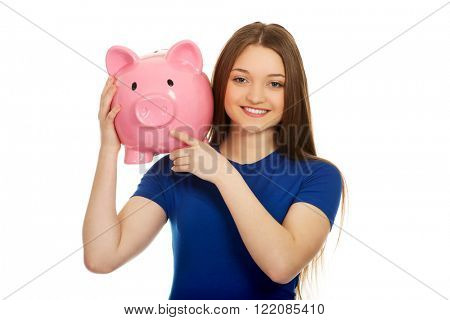 Teenage woman holding piggybank.
