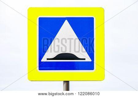 Danger bump road sign against cloudy sky