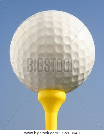 Golfball on yellow tee against blue sky