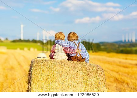 Two little twin kid boys sitting on hay stack or bale and speaking on yellow wheat field in summer. Children having fun together. Active leisure for kids