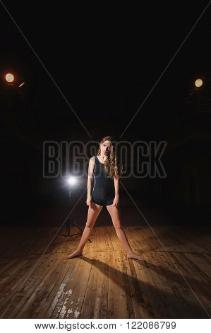Young brunette dancer girl on stage. ballet dancer in black clothes. barefoot dancer.