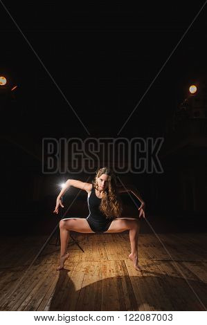 Young brunette dancer girl on stageBallerina, young brunette dancer girl in a black, pointe, dance poses on stage in theater with spotlight. barefoot dancer.
