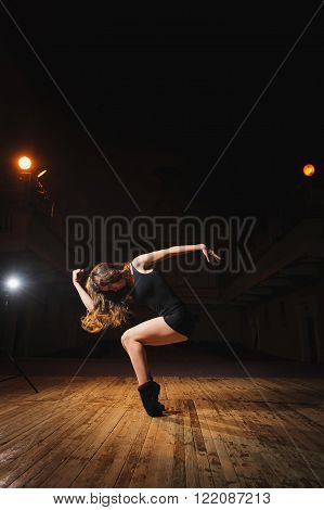 Young brunette dancer girl on stageBallerina, young brunette dancer girl in a black, pointe, dance poses on stage in theater with spotlight.