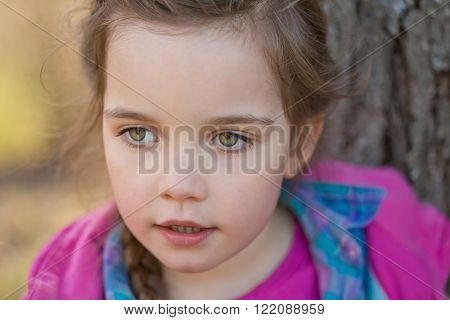 close up of a beautiful girl with green eyes, outdoor portrait