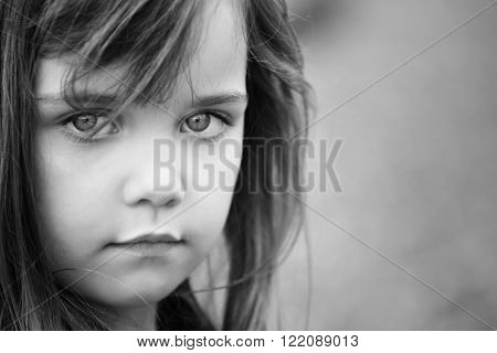 black and white portrait of a little girl with big sad eyes