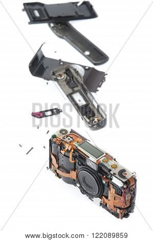 Single disassembled pocket camera with case pieces and exposed electronic parts over white background