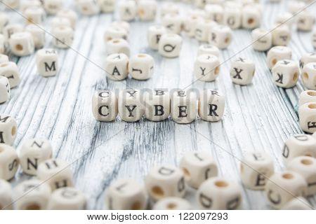 Cyber word written on wood block. Wooden Abc.