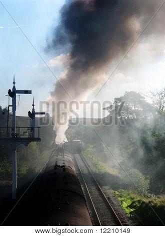 Steam powered passenger train showing dense smoke from engine. Yorkshire, UK