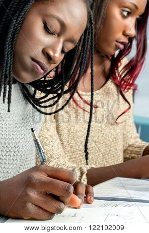 Close up portrait of african teen students doing homework writing with pen on paper. Out of focus girlfriend in background.