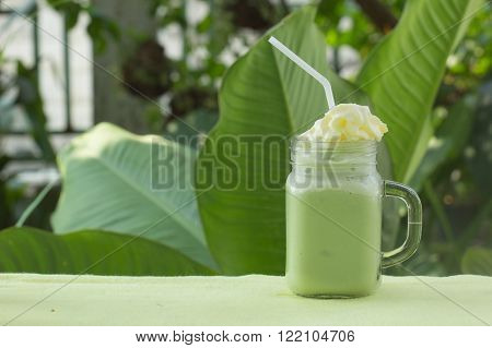 Matcha Green Tea smoothie with whiped cream for refreshment on garden background