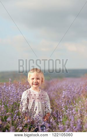 Laughing girl 2-3 year old playing in lavender meadow outdoors. Looking at camera. Childhood.