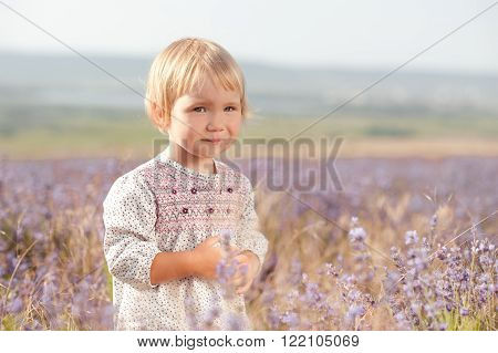 Cute baby girl 2-3 year old playing in lavender field. Wearing trendy dress outdoors. Looking at camera. Childhood.