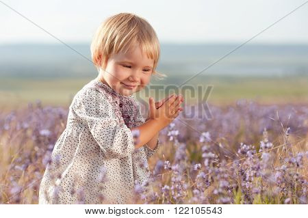 Smiling kid girl 2-3 year old posing in lavender meadow closeup. Playing outdoors. Childhood.