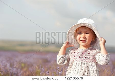 Stylish baby girl 2-3 year old walking in lavender field. Wearing rustic dress and hat. Looking at camera.