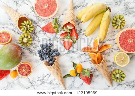 Ice cream waffle cones with fresh ripe fruits