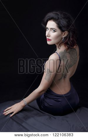 A sexy adult attractive woman sitting back on a bed, with a serious, yet seductive look,  wearing a light evening make-up, a bright red lipstick matching her nails, and sapphire jjewelry