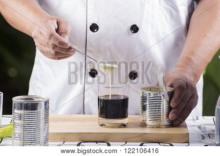 Chef putting condensed milk in to Hot coffee