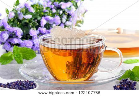 lavender tea with sugar candy in a glass cup