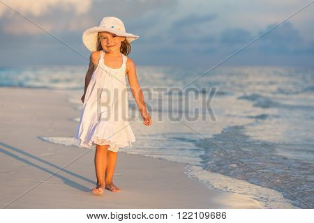 Little girl walking on beautiful ocean beach