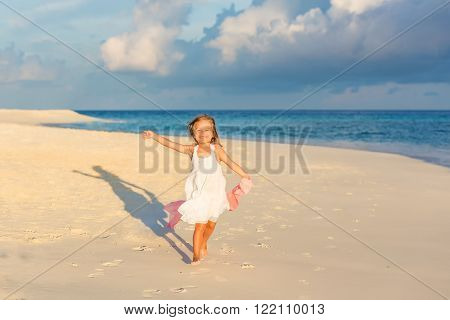 Little girl playing on beautiful ocean beach