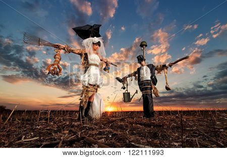 The bride and groom in the form scarecrows at sunset