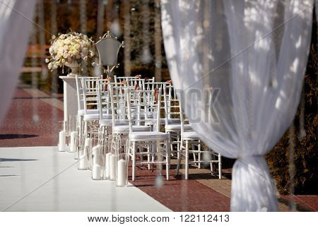 Beautiful chairs and arch at the wedding ceremony.