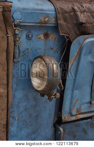 old spotlamp on tractor. iron rust wire blue hanger texture close up