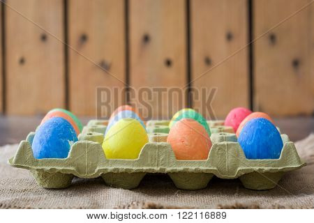 Traditional Easter eggs in carton on wooden background