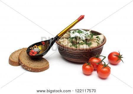 Russian dumplings with sour cream in a clay plate on a white background. horizontal photo.