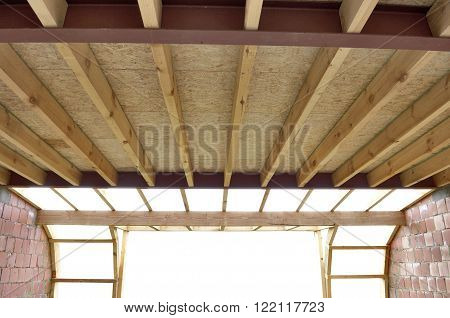 Fiberglass batt insulation between roof trusses at a house construction site