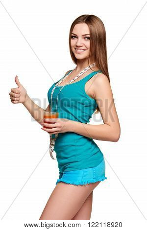 Dieting, slimming, detox cocktail. Happy girl holding a glass of carrot juice, with measurement tape over her neck gesturing thumb up, over white background