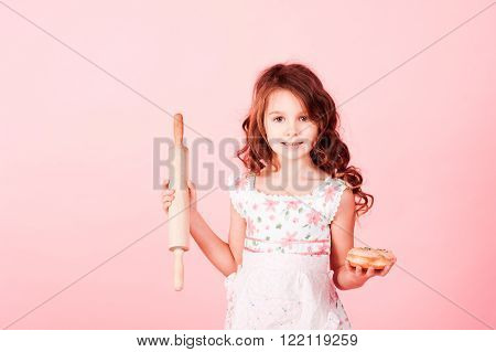 Smiling kid girl 6-7 year old holding plunger and donut over pink. Looking at camera. Cooking child.