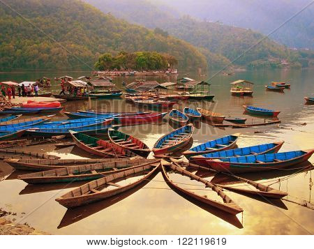 POKHARA NEPAL - MARCH 30: Unidentified tourists do boating on Fewa (Phewa) lake on March 30 2014 in Pokhara Nepal. Pokhara is a popular tourist destination in Nepal.