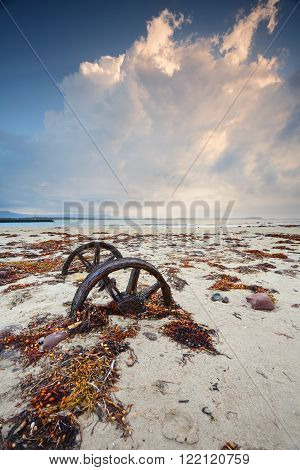Old rusty wheels sitting in the sand on Windang Island