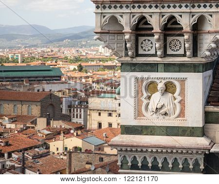 Architectural detail and part of the ornate marble facade of the Cathedral of Florence in Italy or the Cathedral of Santa Maria del Fiore. Dramatic view of Florentine sculptor and painter Andrea Orcagna overlooking the city of Florence.