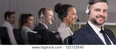 Group of young telemarketers talking with clients in call center corporation