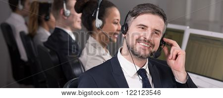 Handsome elegant male telemarketer in call center with headset giving advice to his client