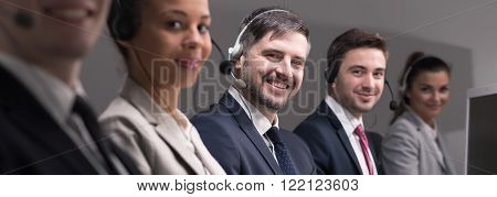 Group of young busy telemarketers with headset calling the clients and selling products