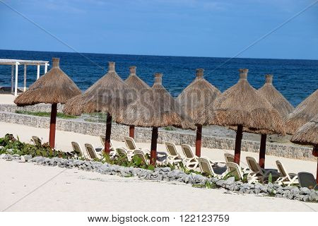 umbrellas on a Mexican beach with deckchairs ,