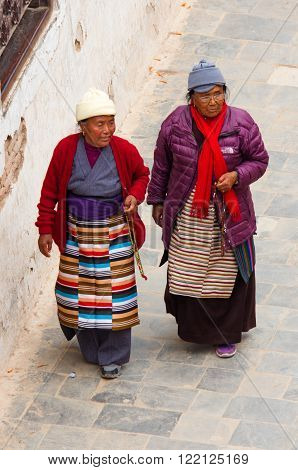 KATHMANDU NEPAL - APR 06: Tibetan and Nepalese people walking around Boudhanath stupa on Apr 06 2014 in Kathmandu. Boudhanath stupa is center of Buddhism pilgrimage in Nepal.
