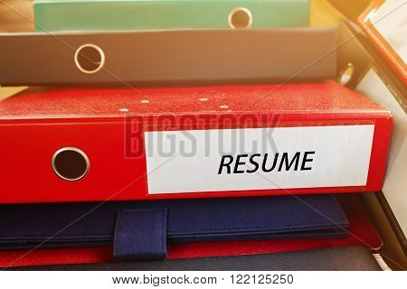 Pile up document file or binder with text resume at spine for business concept background
