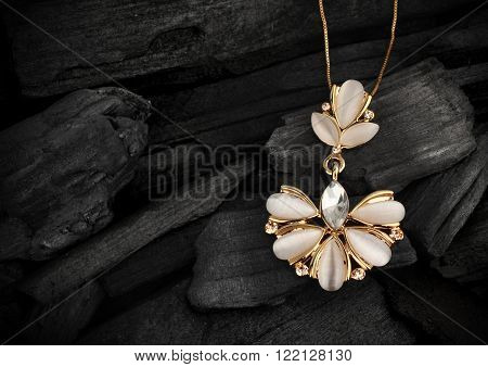 jewelry pendant with gems on darck background