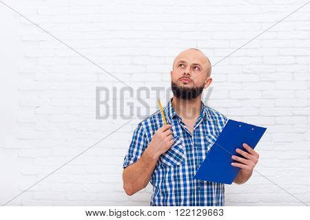 Serious Casual Bearded Business Man Holding Folder Look To Copy Space Pondering Doubtful Office Over White Brick Wall