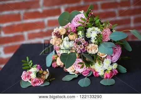 Beautiful bridal bouquet of fresh flowers and grooms boutonniere on old black wooden table at red brick wall background