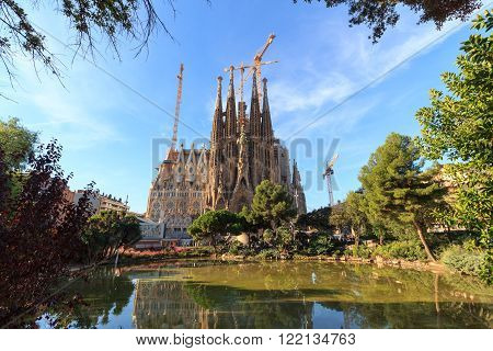 Barcelona, Spain - November 10, 2015: Basilica Sagrada Familia seen from Placa de Gaudi. The church is designed by architect Antoni Gaudi and is still under construction.