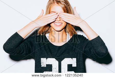 Funny lifestyle portrait beautiful blond crazy girl closes eyes with her hands , in Sweatshirt and white shorts, having fun, emotional and happy mood. Close up. Indoor. Warm color. Hipster.